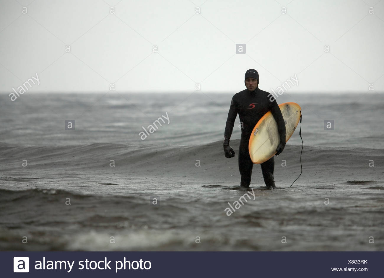 A man stands in knee deep water after facing the harsh canadian surf enviroment. - Stock Image
