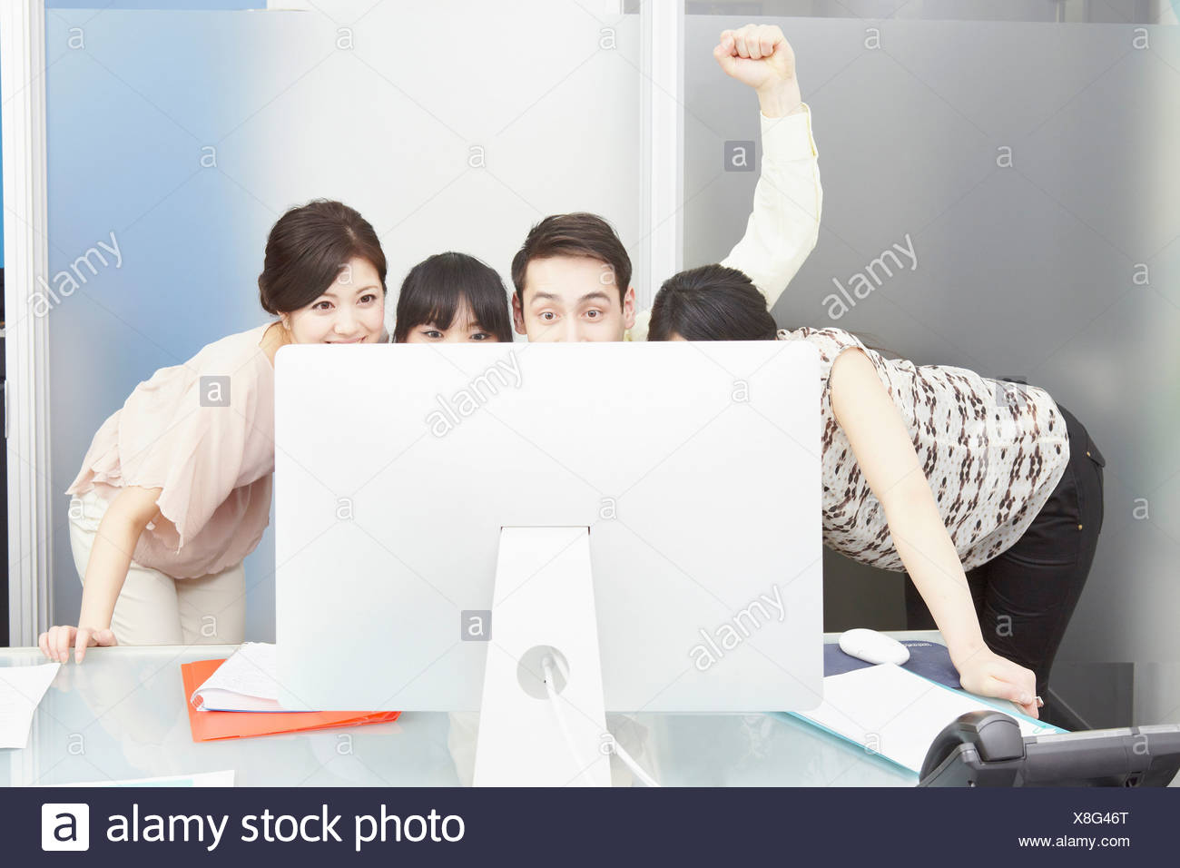 Colleagues looking at computer monitor, man punching the air - Stock Image