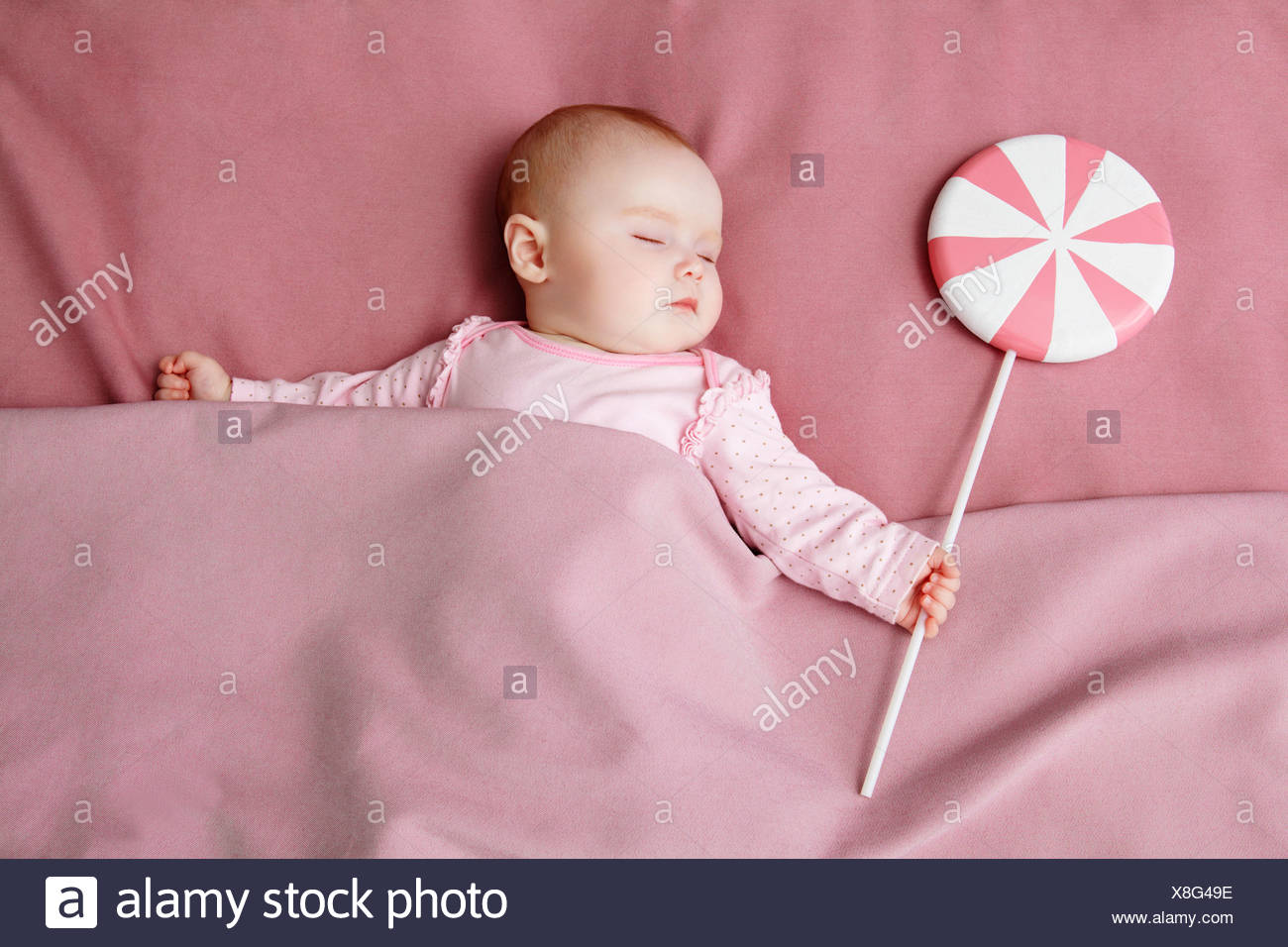 Baby girl sleeping in bed - Stock Image