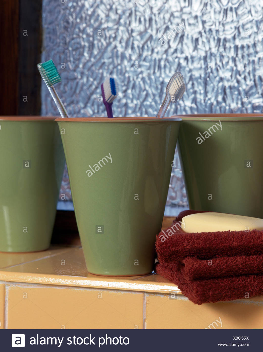 Close-up of green pottery beakers with toothbrushes - Stock Image