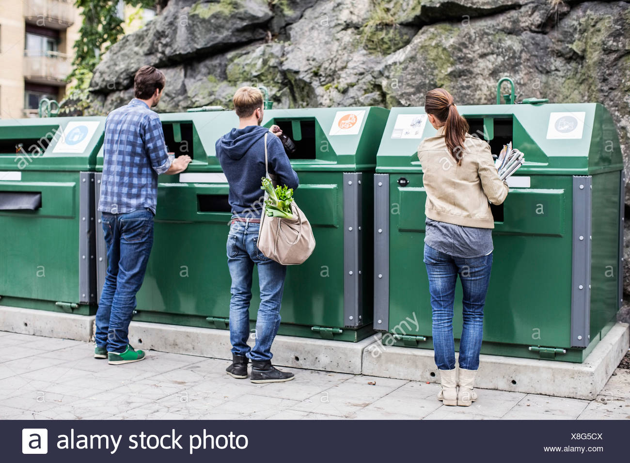 Rear view of friends putting recyclable materials into recycling bins - Stock Image