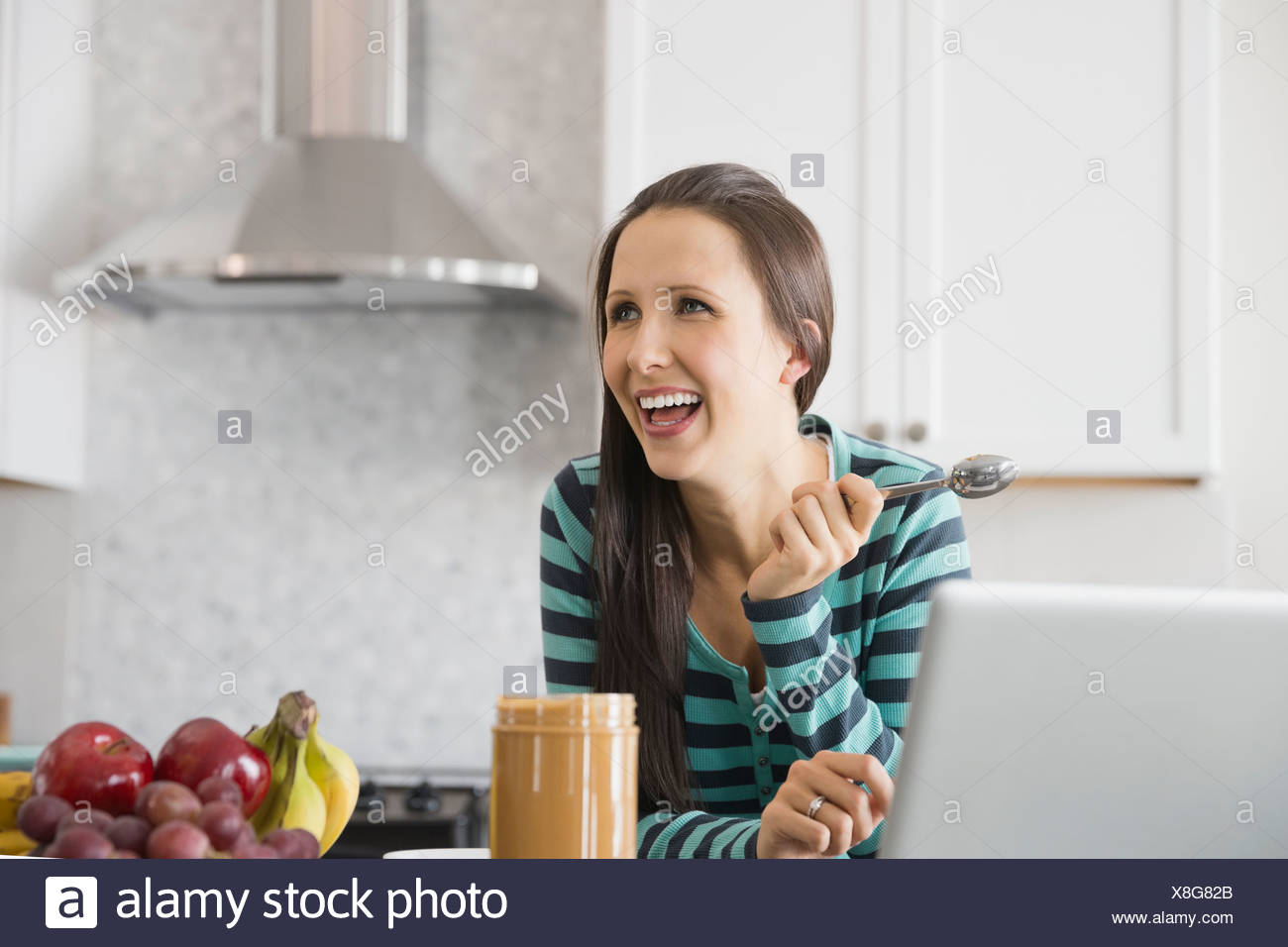 Pregnant woman with peanut butter in kitchen - Stock Image