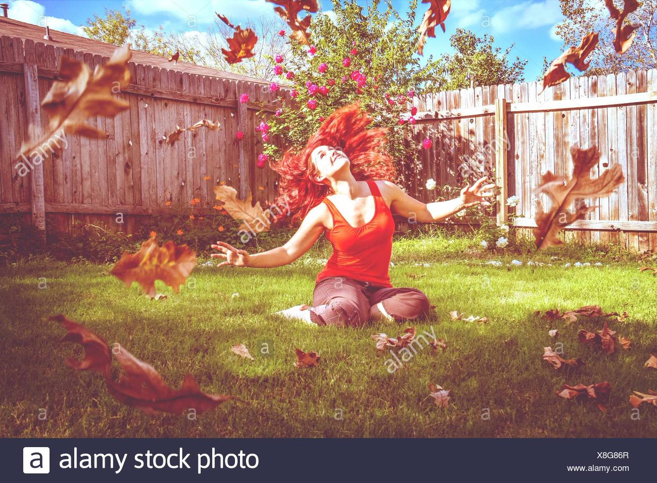 Beautiful Young Woman Looking At Falling Leaves While Relaxing On Field - Stock Image