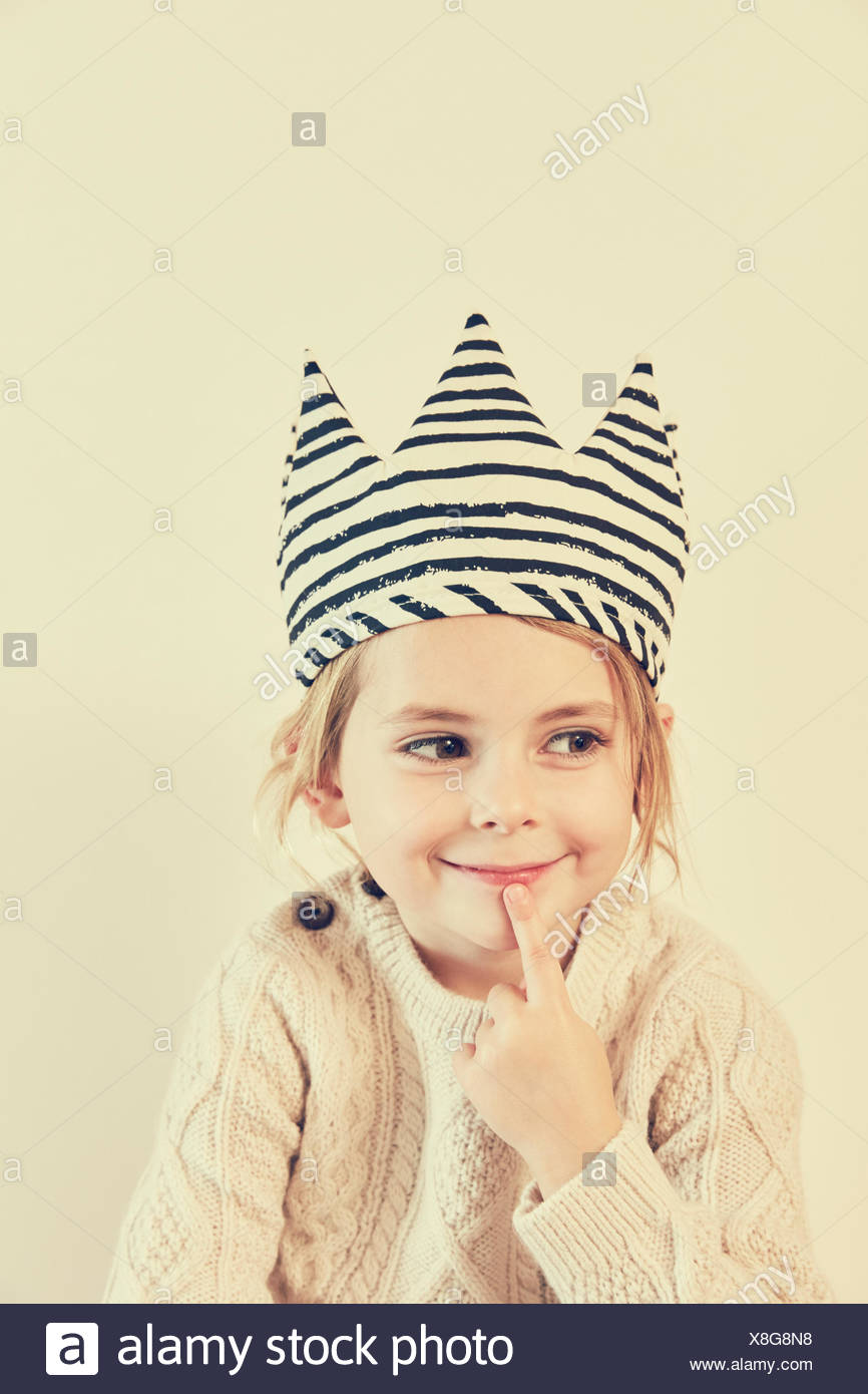Portrait of girl in striped crown with finger on her lips - Stock Image