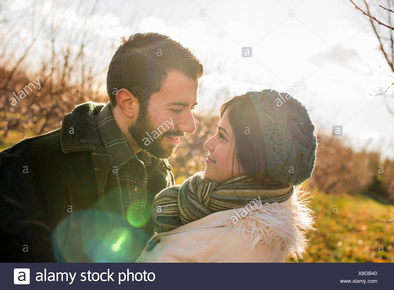 Two people, a couple walking in an orchard in winter. Stock Photo