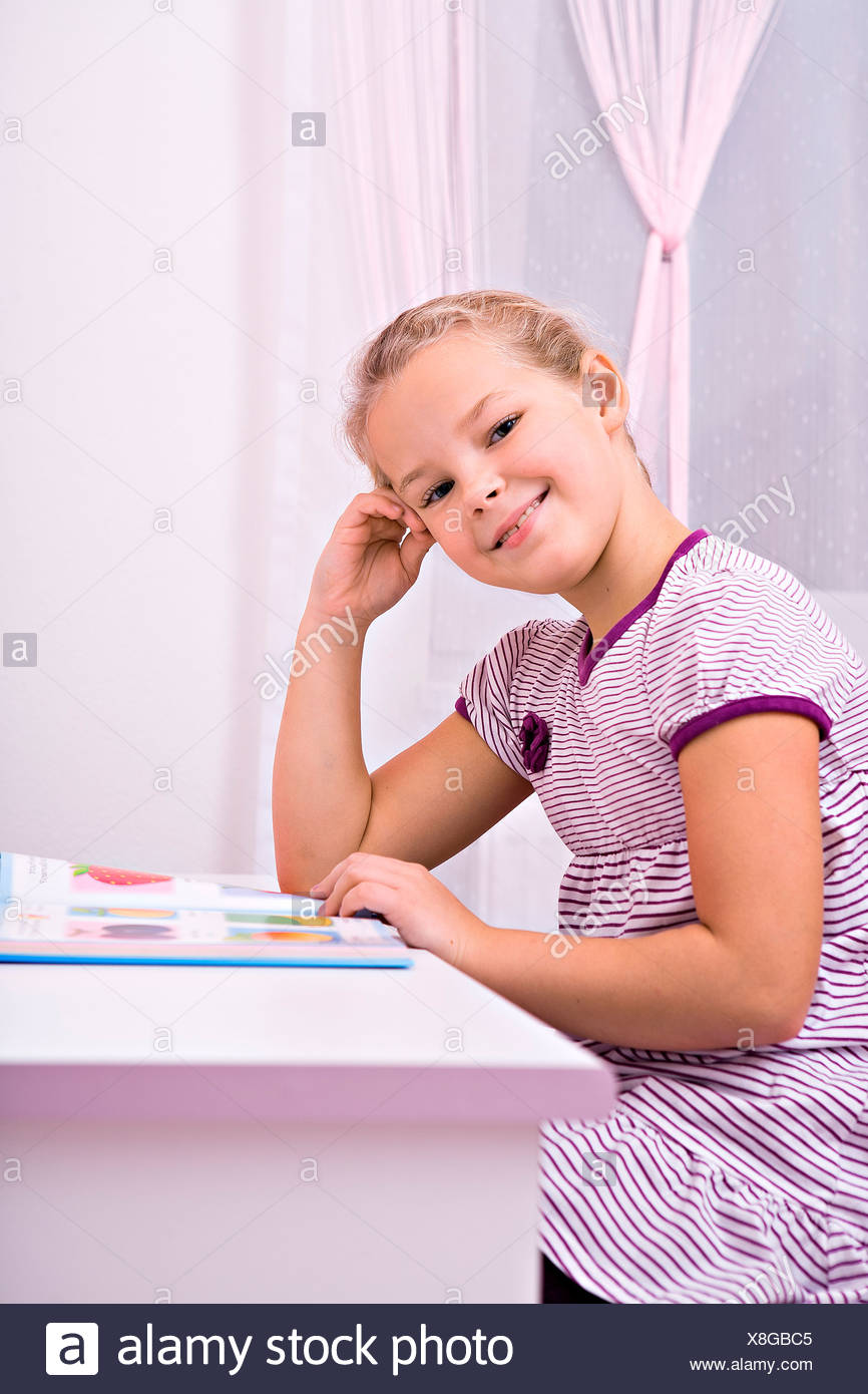 Young schoolgirl doing her homework at her desk - Stock Image