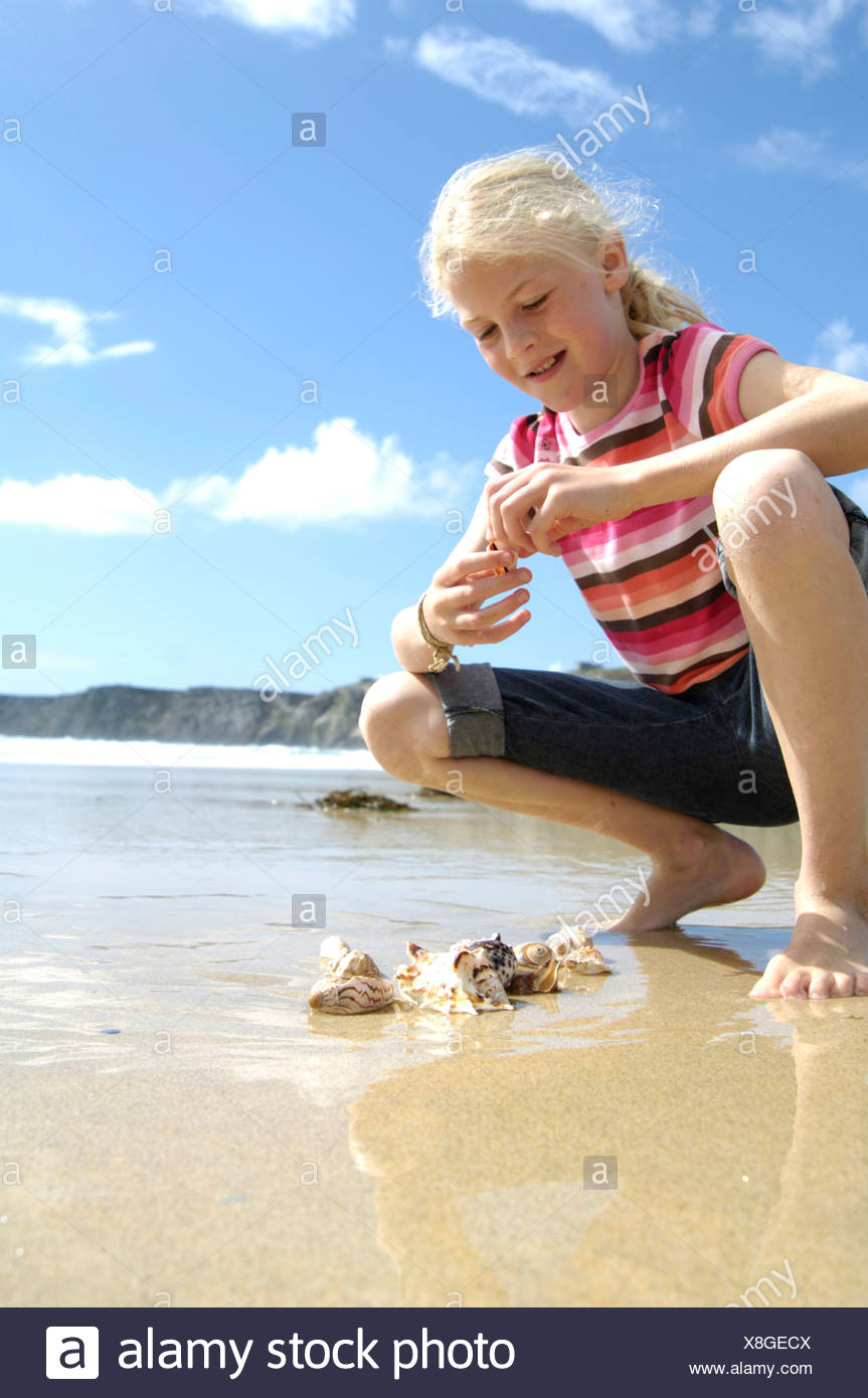 Girl squatting at beach - Stock Image