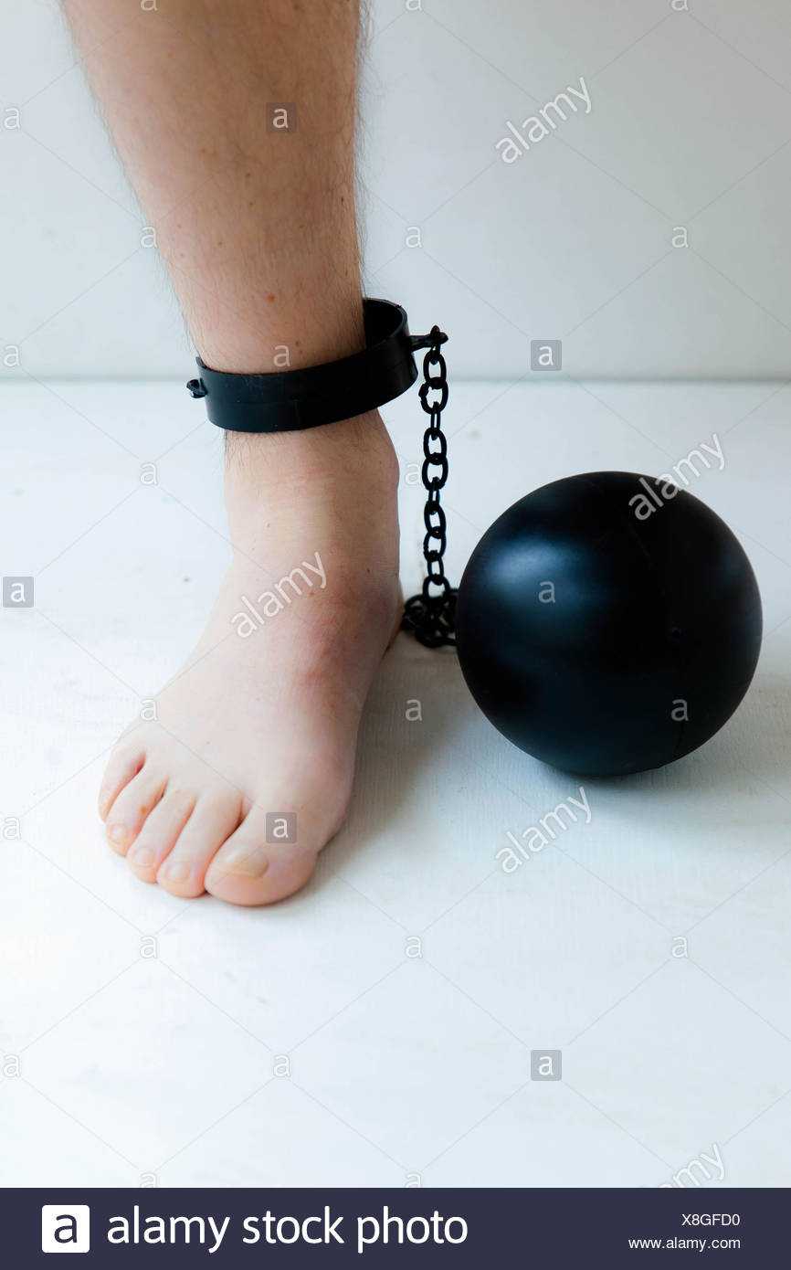 Ball and chain attached to the ankle of a man. - Stock Image