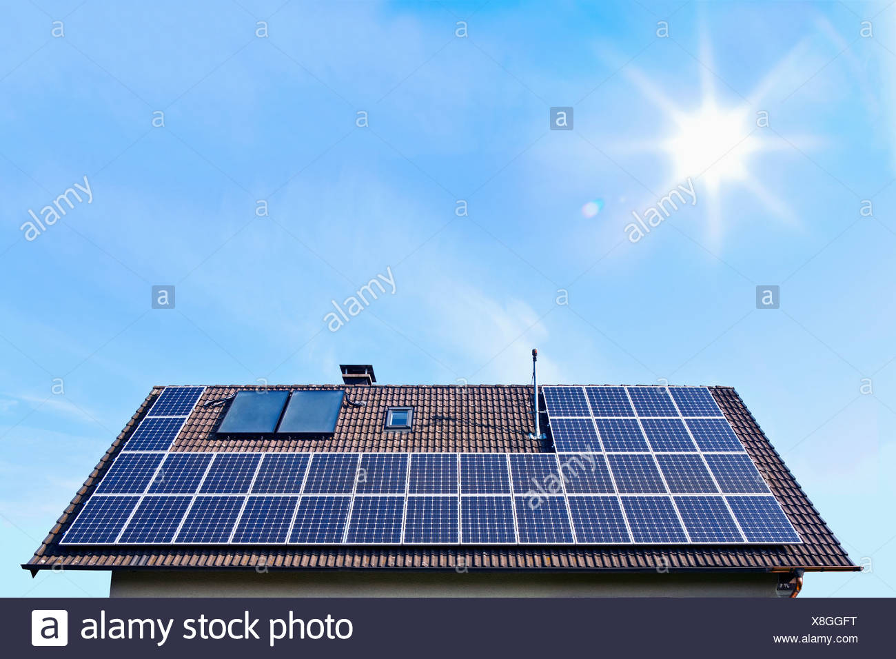 Germany, Solar panels on houseroof in front of blue sky with sun - Stock Image