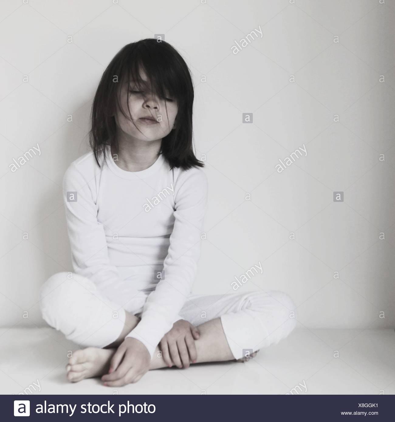Portrait of girl sitting cross-legged with eyes closed - Stock Image