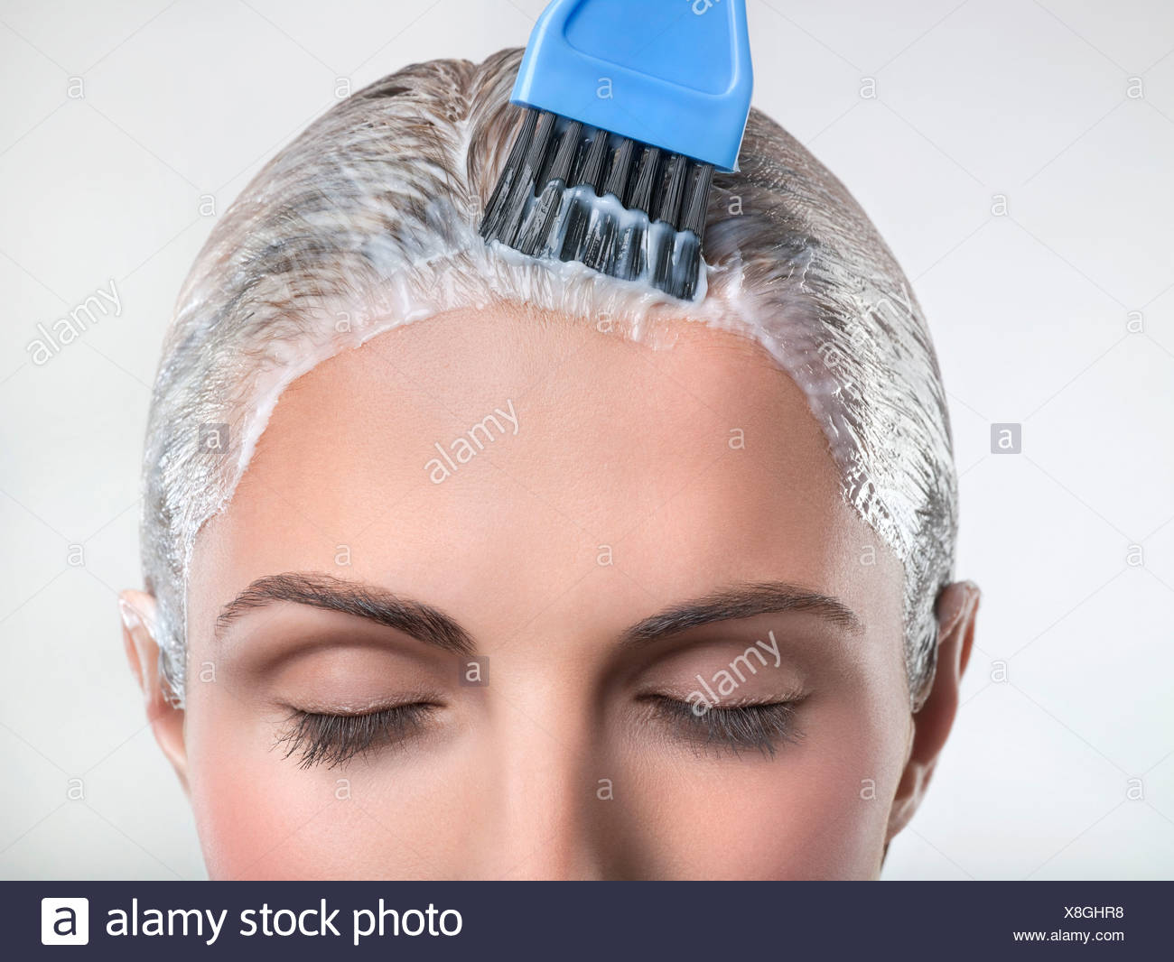Young woman applying hair color - Stock Image