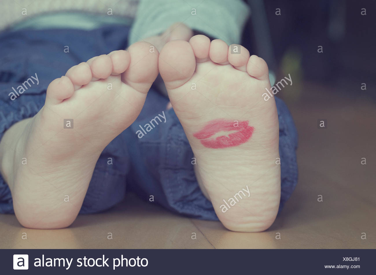 Lipstick kiss on toddler's foot - Stock Image