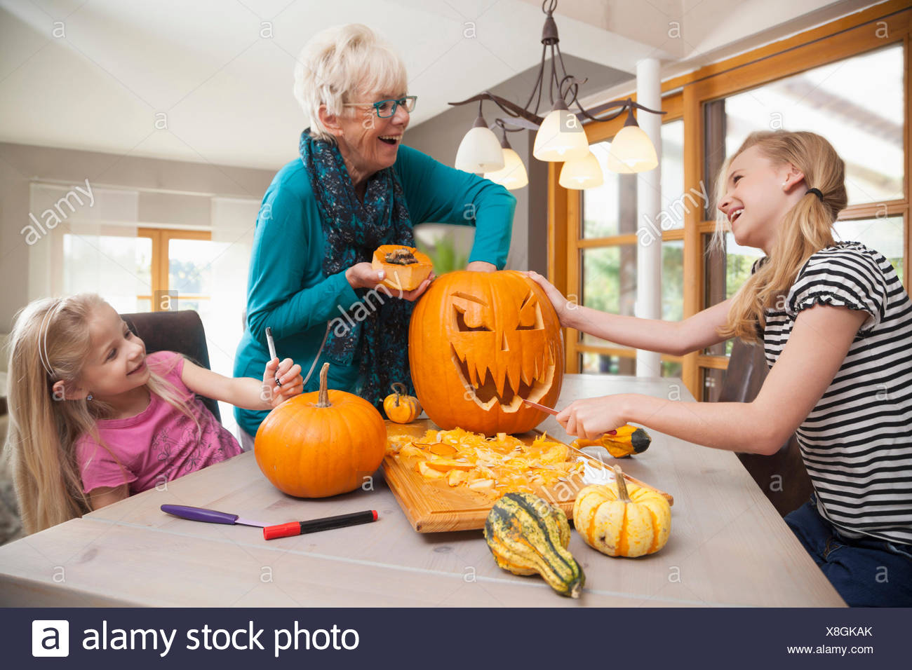 Senior woman carving pumpkin for Halloween with her granddaughters, Bavaria, Germany - Stock Image