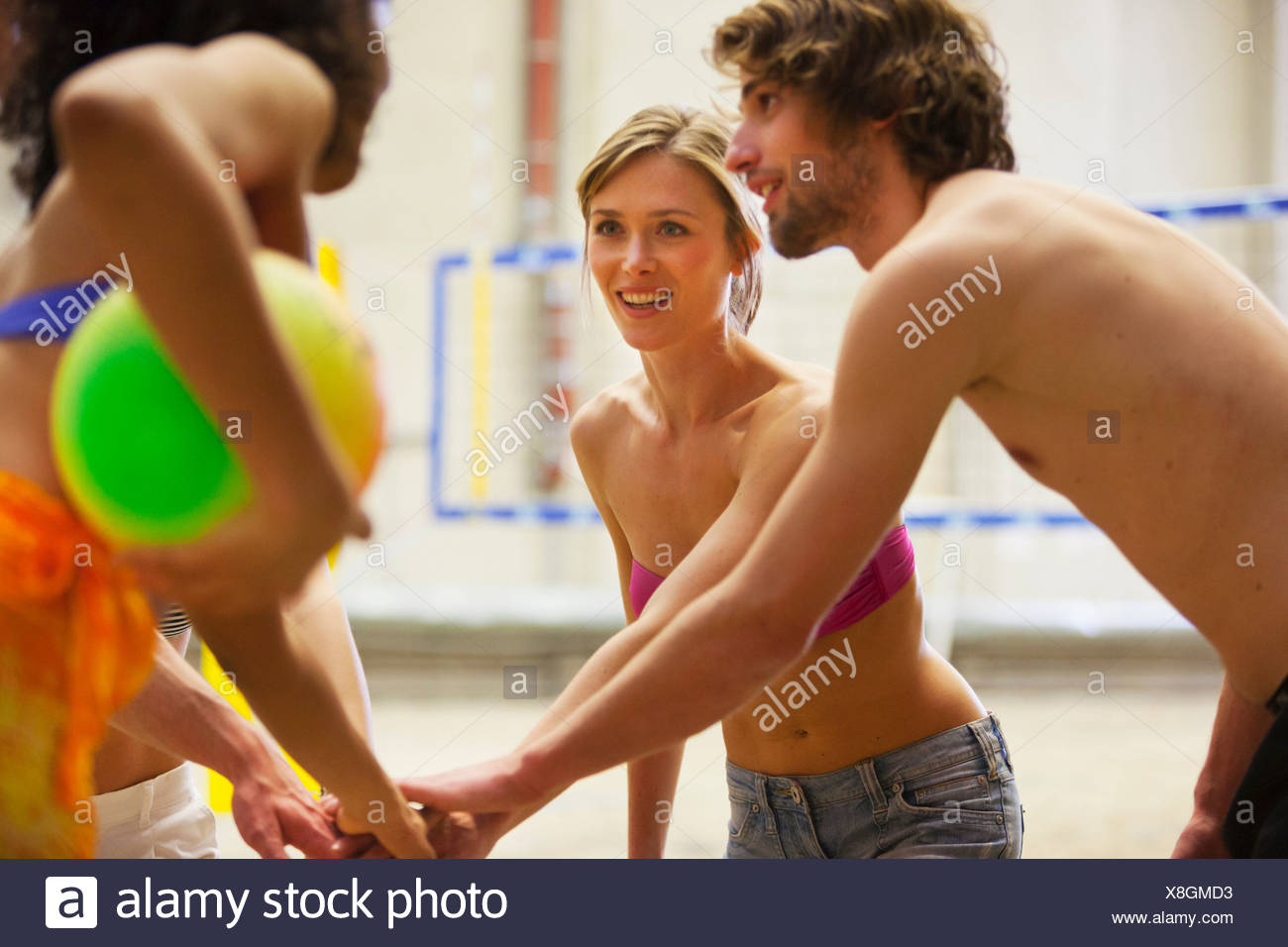 Friends having team talk at indoor beach volleyball - Stock Image