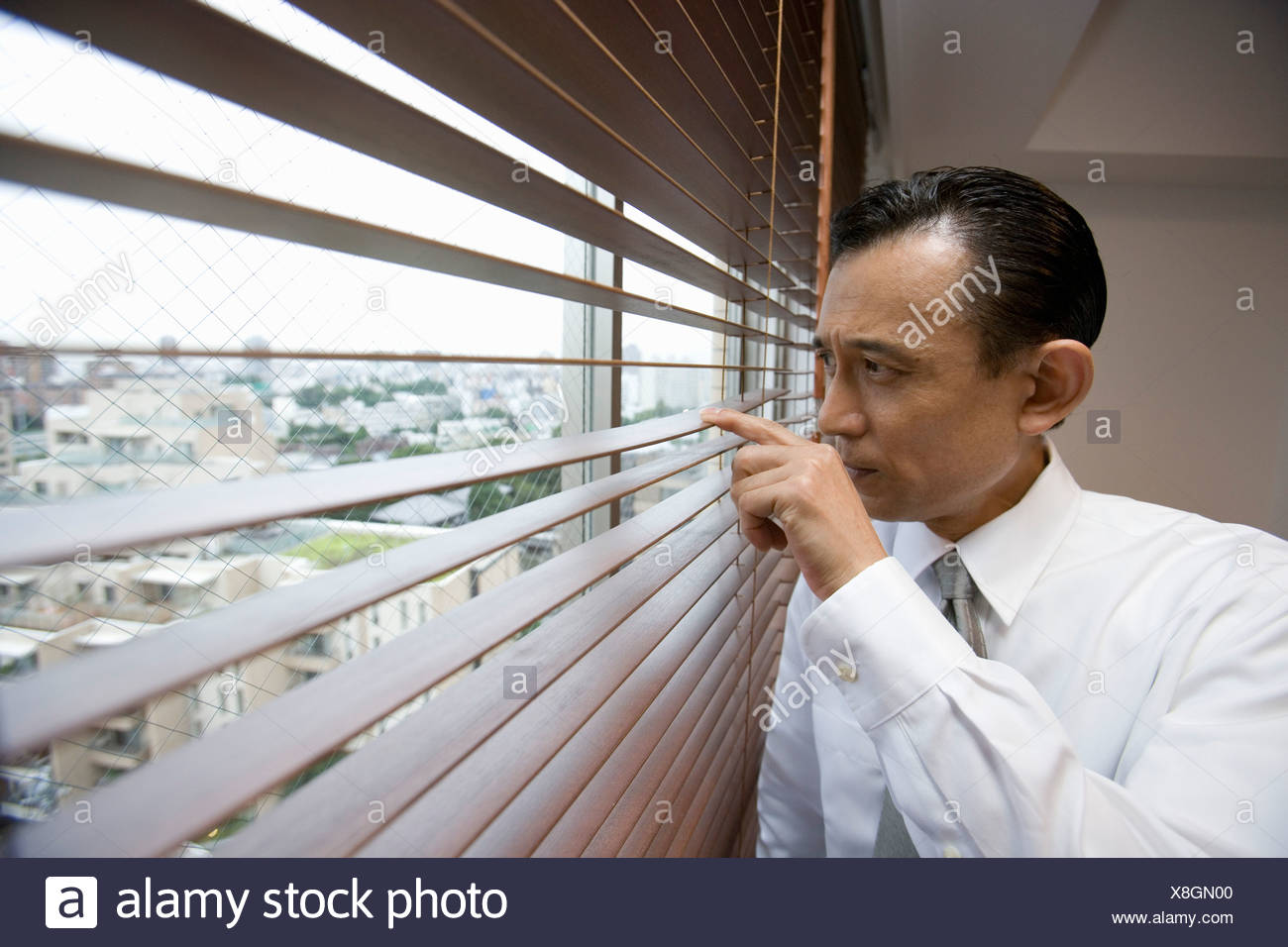A businessman looking through window blinds - Stock Image