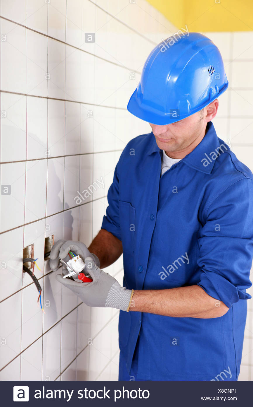 electrician connecting an electrical outlet - Stock Image