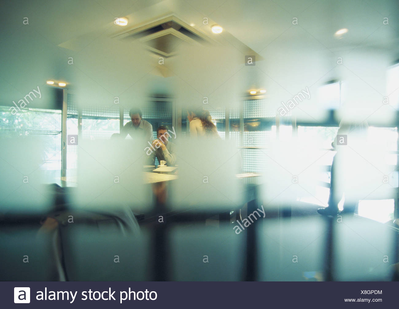 People in conference room, seen through semi-opaque glass wall - Stock Image