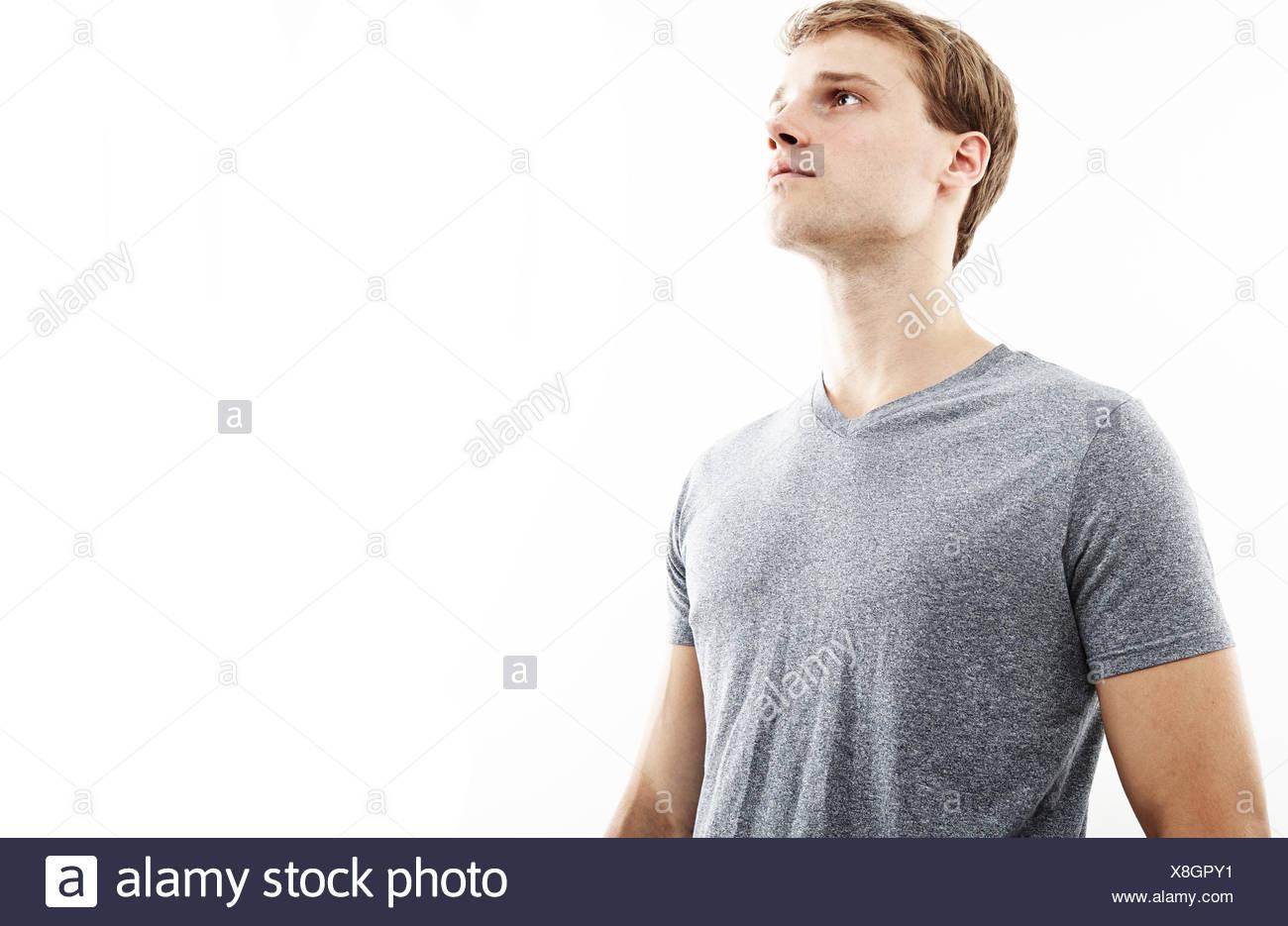 Studio portrait of young man gazing upward - Stock Image