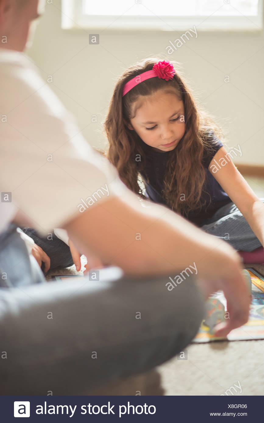 Father and daughter playing board game on sitting room floor - Stock Image