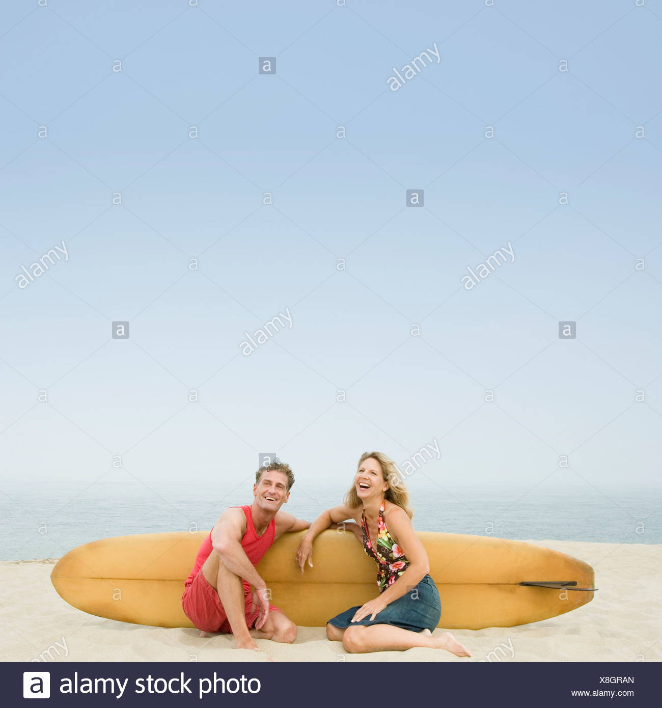 Mature couple sitting on the beach with a surfboard - Stock Image