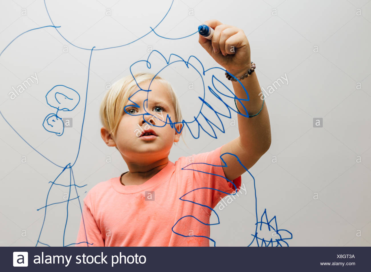Boy drawing with marker pen onto glass wall - Stock Image