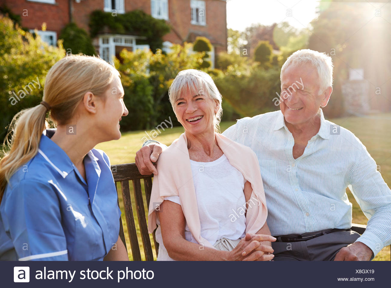 Nurse Talking To Senior Couple In Residential Care Home - Stock Image