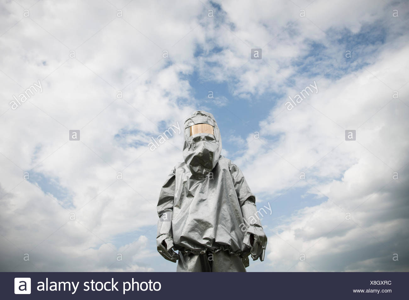 A person in a radiation protective suit standing against a cloudy sky - Stock Image
