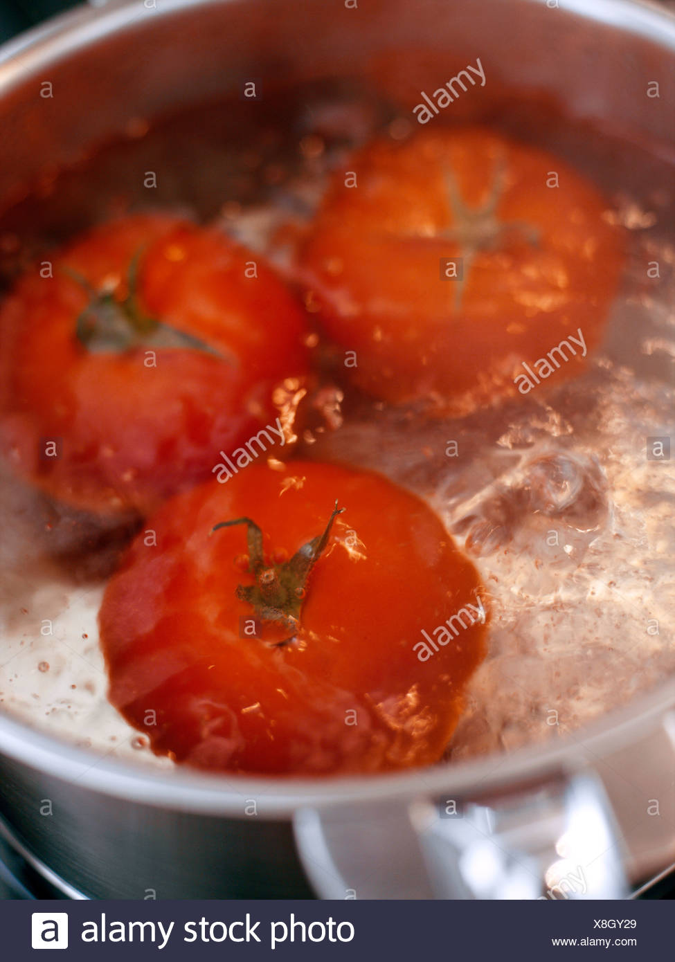 Leaving the tomatoes in the boiling water for a few minutes - Stock Image