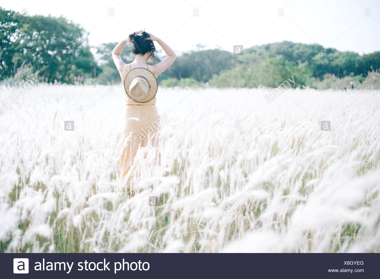 Rear View Of Teenage Girl Walking In Grass Field Stock Photo
