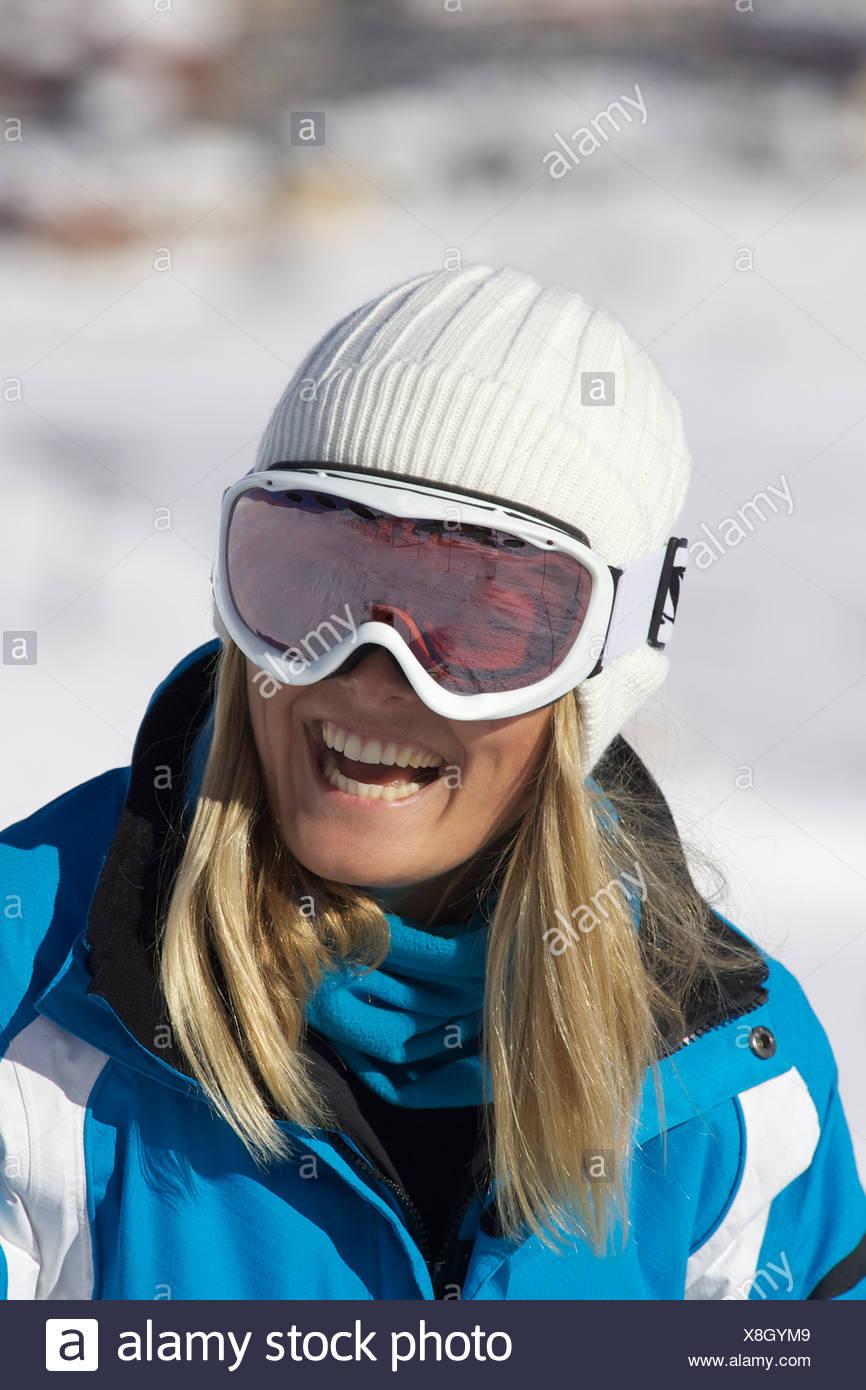 Smiling woman wearing ski goggles - Stock Image