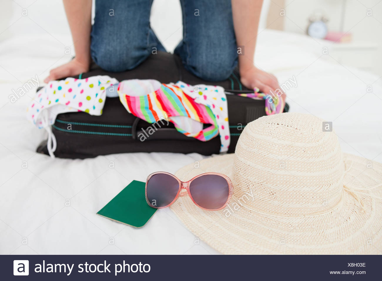 Woman kneeling on suitcase in an attempt to make things fit - Stock Image