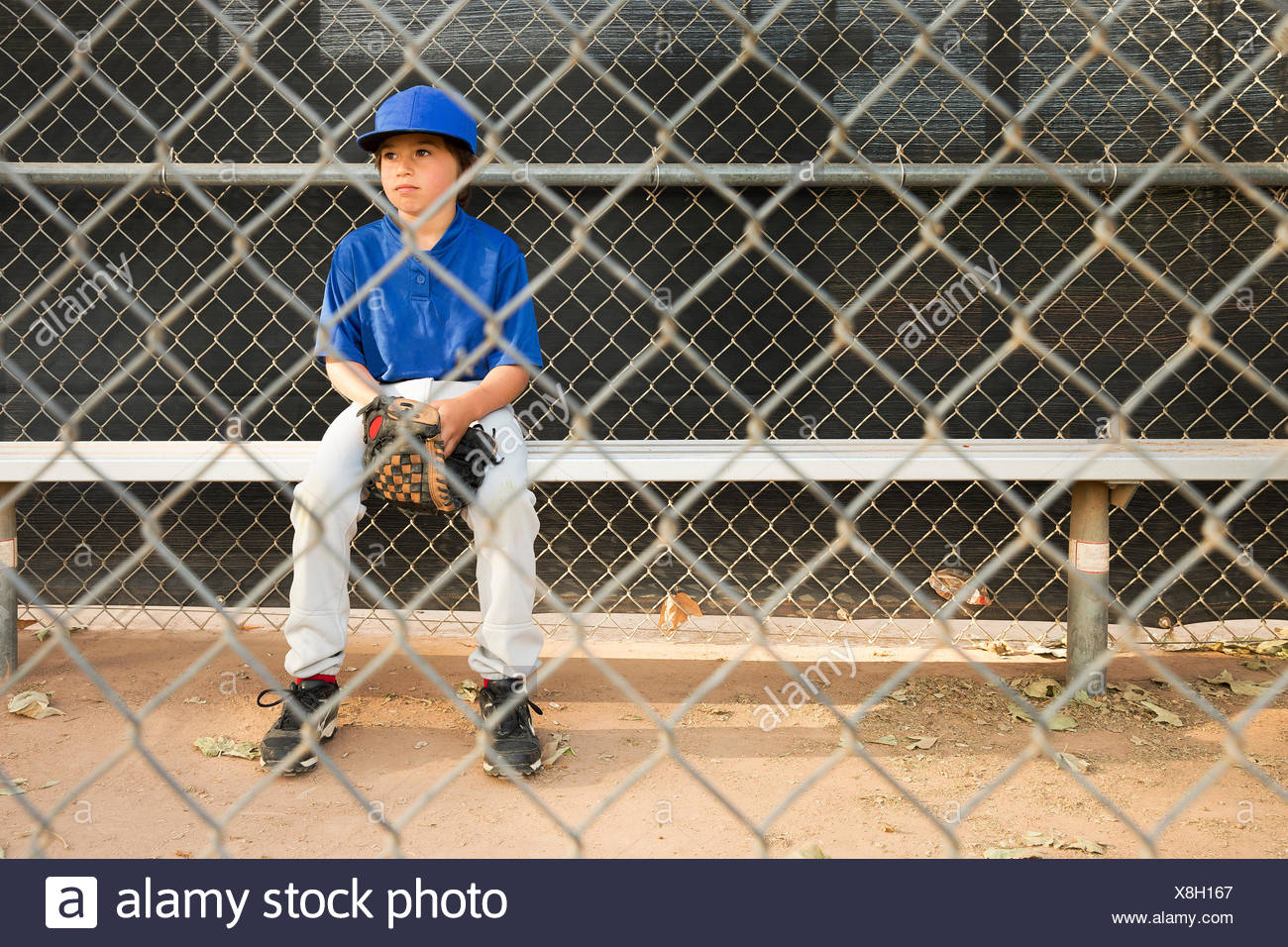 Boy sitting on bench behind wire fence at baseball practise - Stock Image