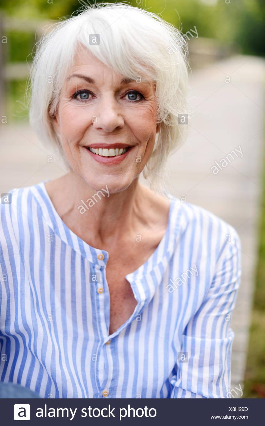 Portrait of smiling white haired senior woman - Stock Image