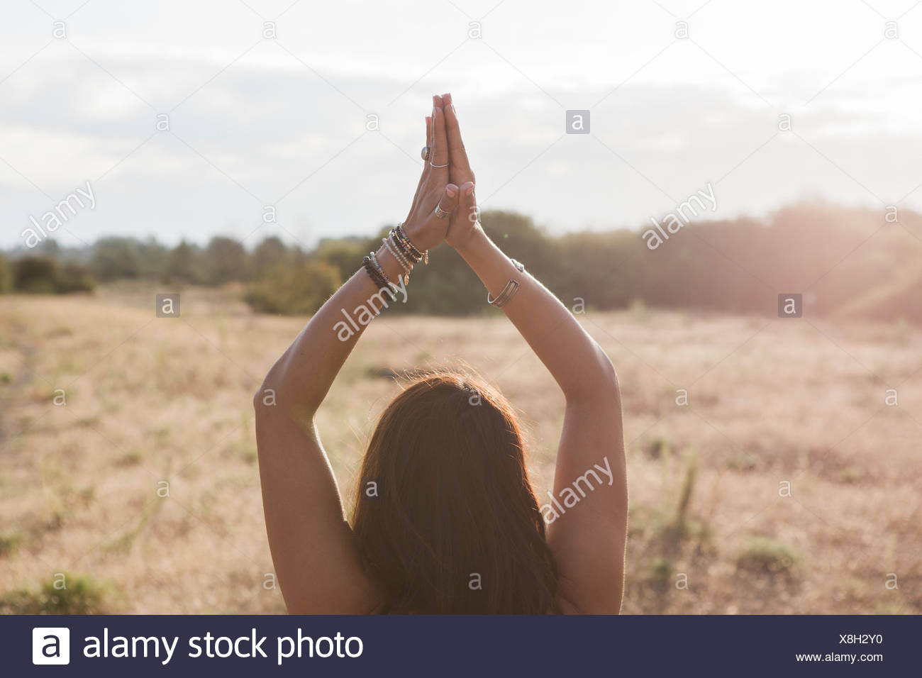 Woman meditating with hands clasped overhead in sunny rural field - Stock Image