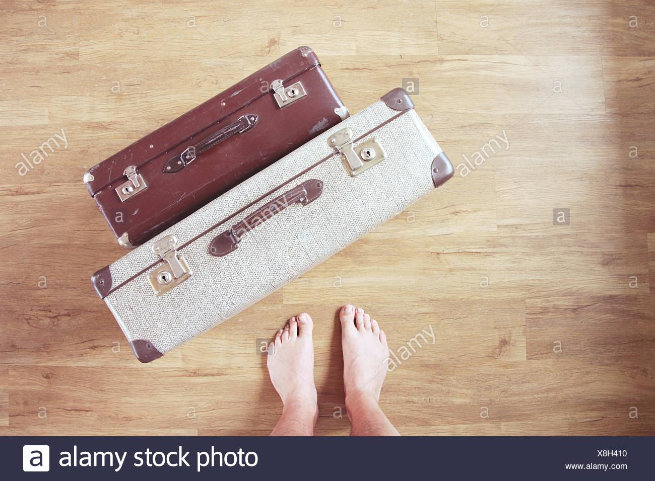 Low Section Of Man With Old-Fashioned Suitcases On Hardwood Floor - Stock Image