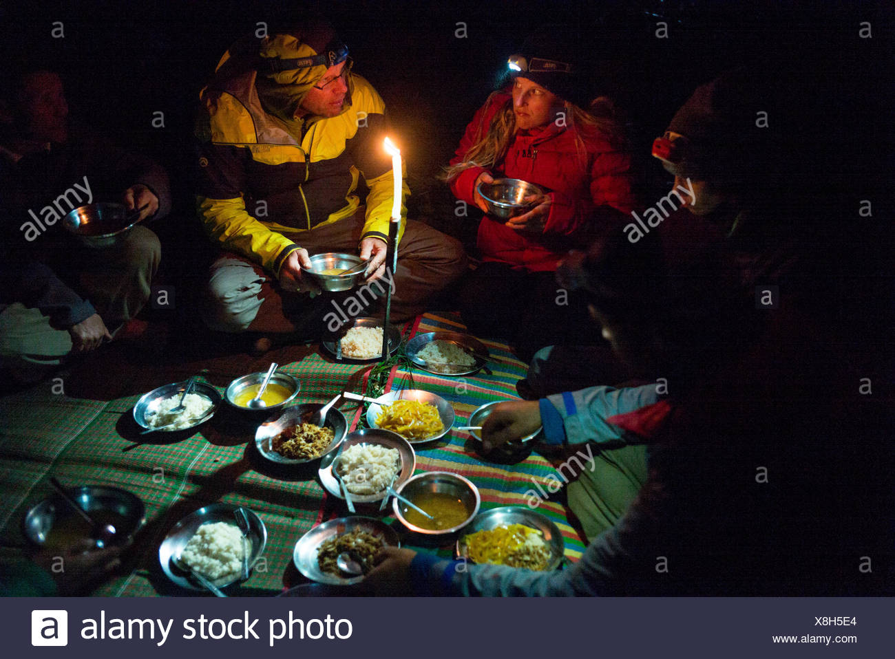 Expedition members sit on a mat and eat a meal by candlelight. - Stock Image