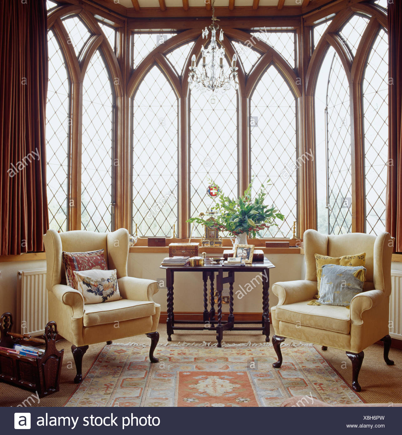 Cream wing-back chairs in front of tall Gothic-style windows ...