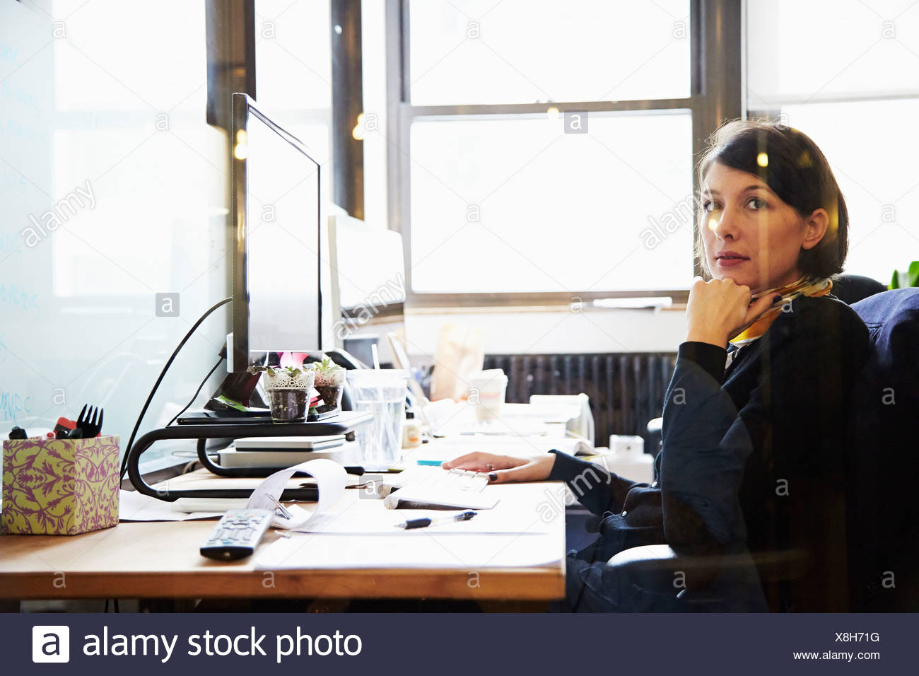 Businesswoman at desk with hand on chin - Stock Image