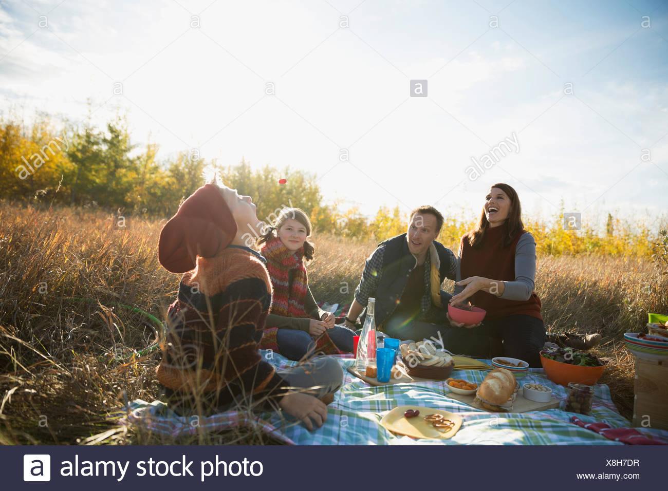 Family enjoying picnic in sunny autumn field - Stock Image