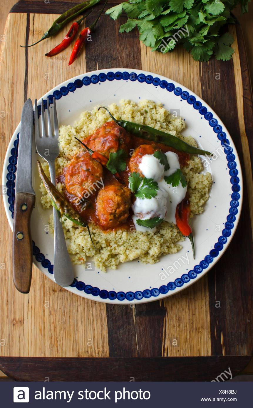 Meatballs in tomato sauce with couscous and chilli peppers. - Stock Image