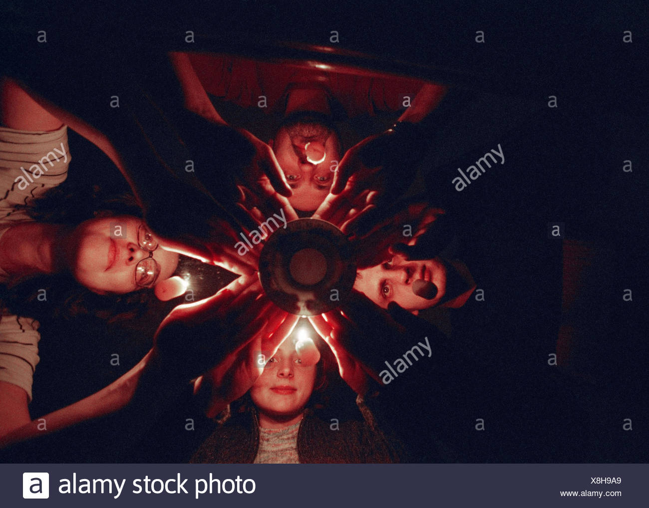 Necromancy, young persons, table, plate, hands, touch, from below spiritualism, occultism, ritual, mind questioning, oracle, mystically, parapsychology, small table back, glass back, 'plate back', session, concentration, strain, expectation, mysticism, my - Stock Image
