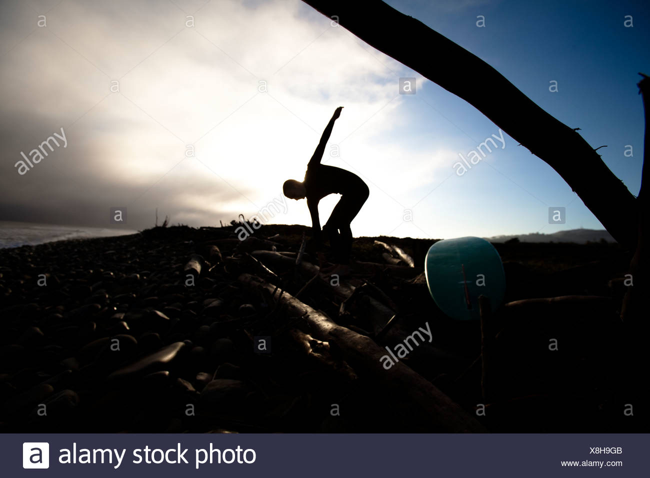 A teenage male stretches before he goes surfing in Ventura, California. - Stock Image