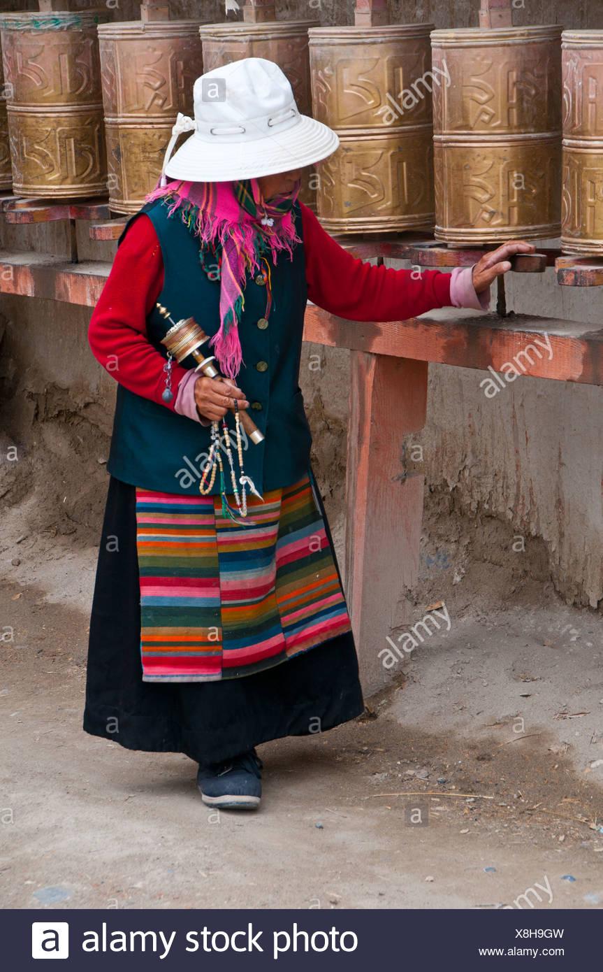 Old woman turning prayer wheels, kingdom of Guge, Western Tibet, Tibet, Asia Stock Photo