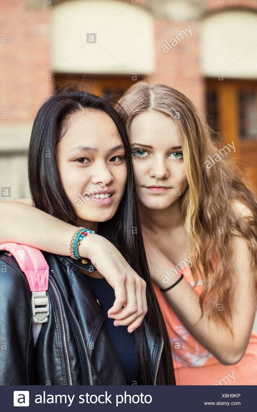 Portrait of female friends on high school schoolyard - Stock Image