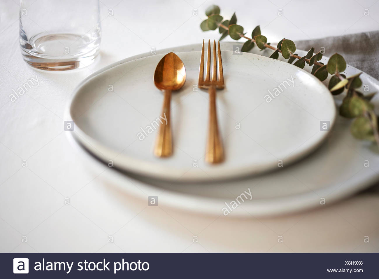 Minimal Table Setting With Handmade Off White Plates Gold Silverware And Linens Stock Photo Alamy
