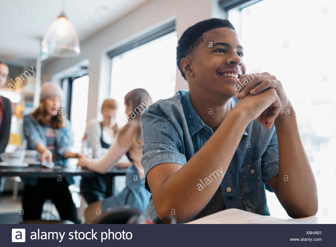 Smiling,confident African American high school boy student studying in cafe - Stock Image
