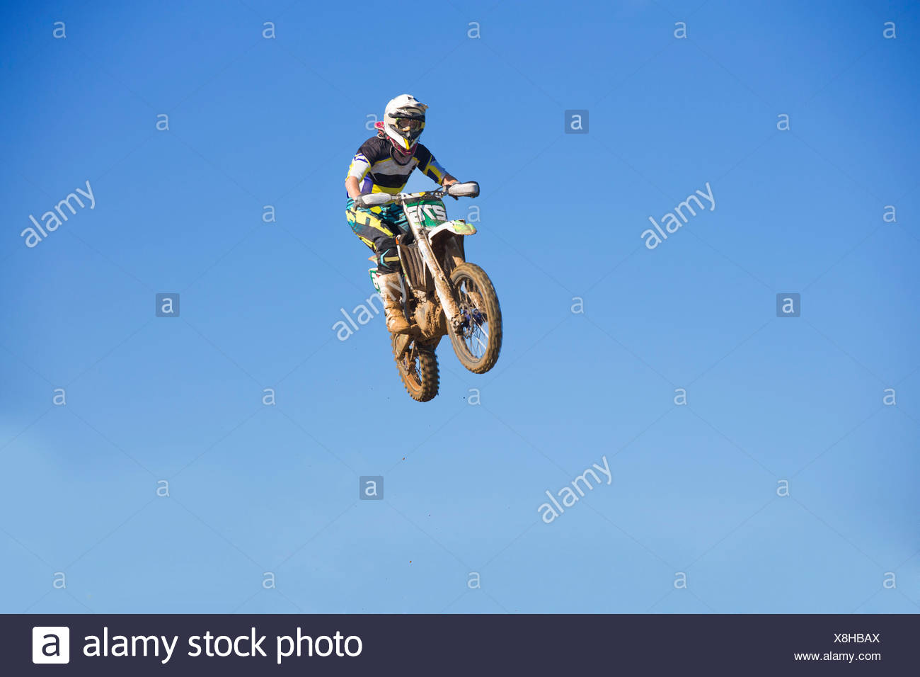 Young male motocross racer jumping mid air against blue sky - Stock Image
