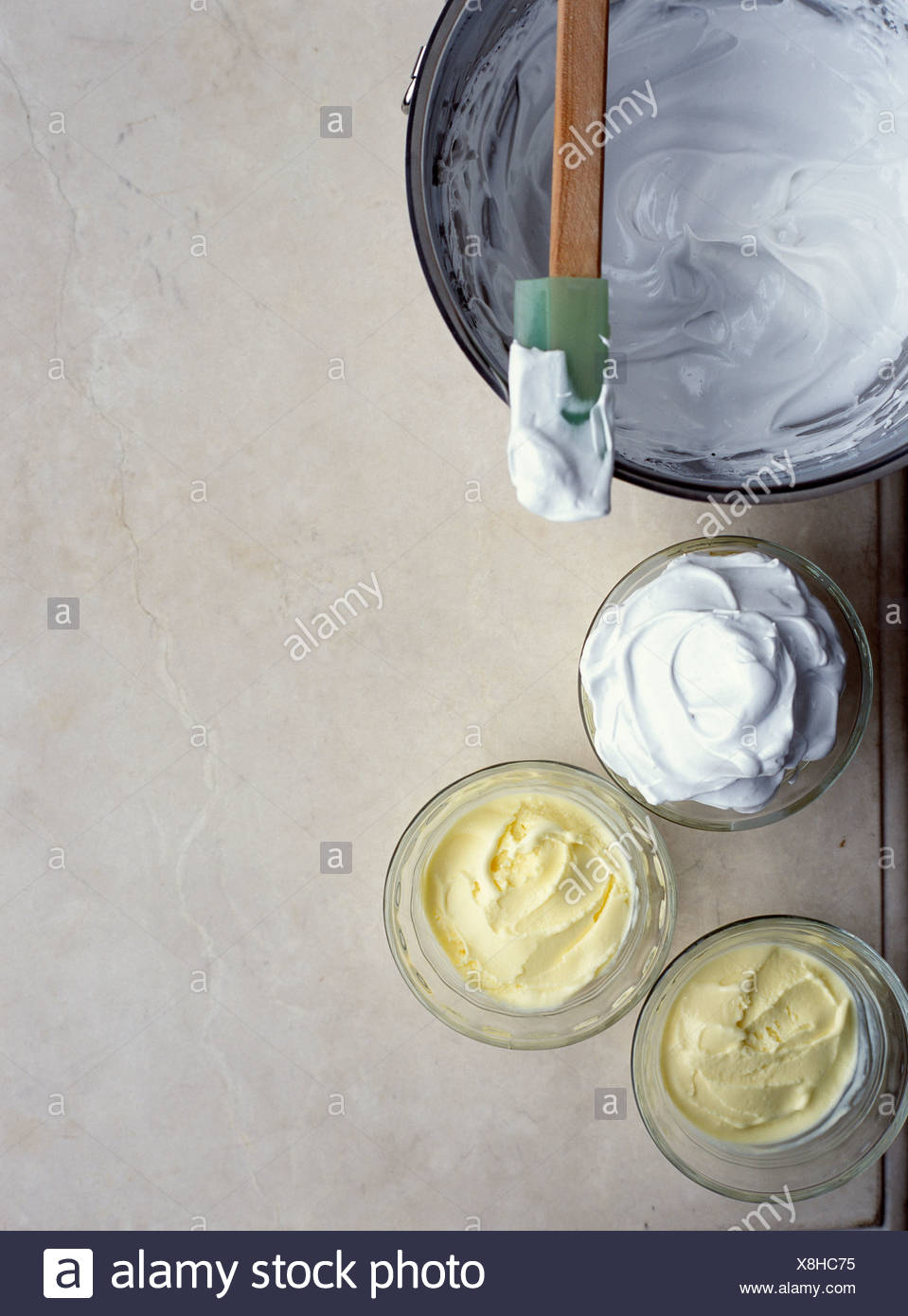Adding the meringue to the verrines half full of lemon sorbet - Stock Image