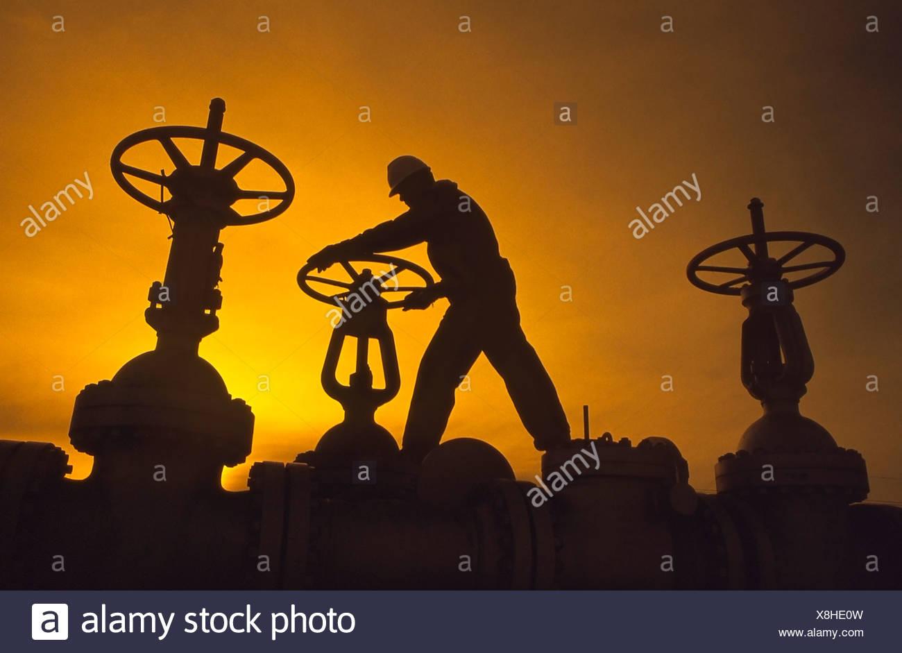 Oil industry worker turning valve on pipeline - Stock Image