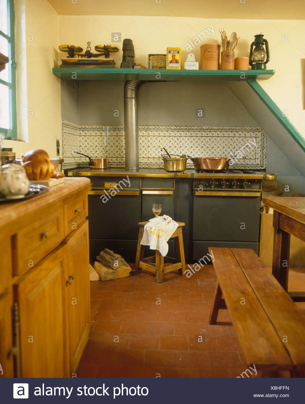 Range Oven And Quarry Tiled Floor In French Country Kitchen With Rustic Wooden Bench Table
